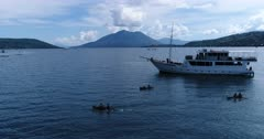 Drone footage of kids floating on tiny local boats next to a liveaboard boat in a bay of Alor island with Pura island and its volcano shape in the background. The camera is turning around the dive boat showing the kids paddling in their small wooden boats.
