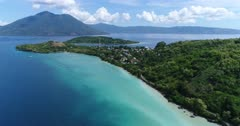 Drone footage of the coast of Alor kecil island with its luxuriant tropical vegetation and Pura island with its volcano shape in the background. The camera is descending over the water showing the coast and its shallow water and is tilting up slowly.