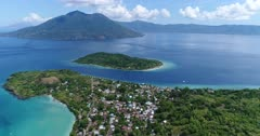 Drone footage of the coast of Alor kecil island with its village built close to the water and luxuriant tropical vegetation, Pura island with its volcano shape is in the background. The camera is showing the small village with the volcano in the background and is panning while descending.