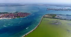 Drone footage of parasailing and other water activities in front of Tanjung Benoa beach in Nusa Dua with Bali toll road over the water behind and the south of Serangan Island. The camera is starting from Nusa Dua and is panning towards the sea and Serangan Island with the waves crashing on its coast.