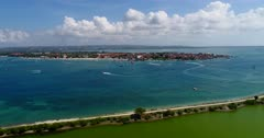 Drone footage of parasailing and other water activities in front of Benoa bay in Nusa Dua. The camera is facing the end of Tanjung Benoa beach and is descending over the green water of the pond in the south of Serangan island.