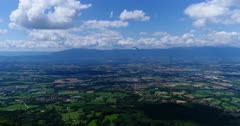 Drone footage of Geneva beautiful countryside with the Jura mountain in the background and a paraglider turning in front. The camera is facing Geneva countryside and is slowly going backward.
