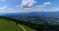 Drone footage of Geneva beautiful countryside with the Jura mountain in the background, the Saleve in the foreground and a paraglider passing in front. The camera is facing Geneva countryside and is slowly going forward.