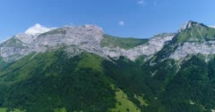 Drone footage of the mountains with their rocky top and dense forest side and Montmin village close to Annecy lake. The camera is facing up to the rocky montain top and is tilting down towards the village.