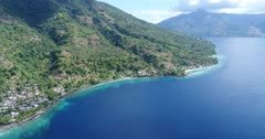 Drone footage of the rocky coast of Pura island with its luxuriant tropical vegetation, shallow coral reef and a village built along its coast. The camera is going over the water sideways along the coast of the island while descending towards the village.