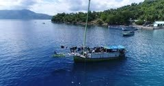 Drone footage of a fishing boat floating in a bay of Pura island with its luxuriant tropical vegetation, shallow coral reef and houses built along its coast. The camera is turning around the boat, going from one side to the other.