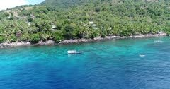 Drone footage of a man paddling in a small boat with outtriggers along the coast of Pura island with its luxuriant tropical vegetation, shallow coral reef and houses built along it. The camera is starting following the small boat and then is going away from it while ascending.