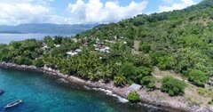 Drone footage of the rocky coast of Pura island with its luxuriant tropical vegetation, shallow coral reef and a village built along its coast. The camera is showing the houses built between threes and is descending while going towards palm trees growing along the coast.