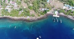 Drone footage of coconut trees and the tropical vegetation growing along the volcanic coastline of Pura island and its colorful shallow coral reef. The camera is facing down at the beautiful turquoise shallow water and is turning while tilting up showing a dive boat anchored close by.