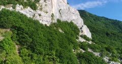 Drone footage of the Saleve mountain near Geneva with its rocky vertical cliff and forest slope. The camera is ascending straight next to the limestone vertical cliff.