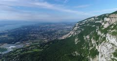Drone footage of the countryside around Geneva, the Leman lake and the Saleve mountain with its rocky vertical cliff and forest slope. The camera is doing a full 360 degrees panning next to the mountain.
