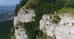 Drone footage of rocky vertical cliffs of the Saleve mountain with countryside below. The camera is going along the cliffs very close.
