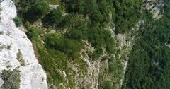 Drone footage of rocky vertical cliffs of the Saleve mountain with countryside below. The camera is facing down at birdview angle and is tilting up.