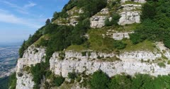 Drone footage of rocky vertical cliffs of the Saleve mountain. The camera is going towards the cliffs very close.