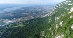 Drone footage of rocky vertical cliffs of the Saleve mountain with Geneva and the countryside around the Leman lake below. The camera is going along the cliffs and is panning towards Geneva city.