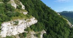 Drone footage of rocky vertical cliffs of the Saleve mountain and its forest slopes. The camera is going along the cliffs towards the forest sides.