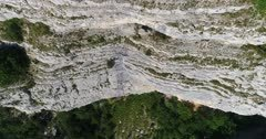 Drone footage of rocky vertical cliffs with trees of the Saleve mountain. The camera is going along the cliffs facing down at birdview angle.