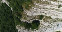 Drone footage of rocky vertical cliffs with trees of the Saleve mountain. The camera is going along the cliffs facing down at birdview angle and then tilting up.