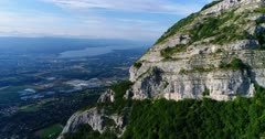 Drone footage of the countryside around Geneva and the Leman lake close to the rocky vertical cliffs of the Saleve mountain. The camera is going away from Geneva passing behind the mountain.