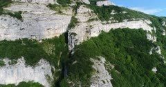 Drone footage of the Saleve mountain near Geneva with its rocky vertical cliff and forest slope. The camera is ascending straight next to the limestone vertical cliff before panning towards the top.