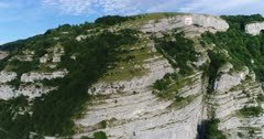 Drone footage of rocky vertical cliffs with trees of the Saleve mountain. The camera is going towards the mountain while panning.