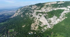 Drone footage of the Saleve mountain near Geneva with its rocky vertical cliff and forest slope. The camera is facing the mountain and is panning while tilting down towards the base of it