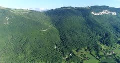 Drone footage of the Saleve mountain near Geneva with its rocky vertical cliff and forest slope. The camera is panning the whole mountain.