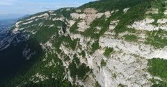 Drone footage of the Saleve mountain near Geneva with its rocky vertical cliff and forest slope. The camera is going along the mountain
