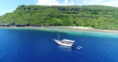 Drone footage of a deserted beach surrounded by tropical vegetation and colorful coral reef in the north of Dawera island, Indonesia. The camera is going along the rocky coast and the shallow reef and then is going away showing the deserted beach as well as a boat anchored in front of it.
