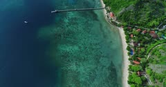 Drone footage of a lagoon with sandy beach, turquoise water, coral reefs, hotels built on the coast and hilly tropical surrounding in the north of Labuan Bajo, Flores. The camera is facing down at the water and is going along the coast while tilting up.
