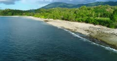 Drone footage of the coast of south-west Sumbawa around Maluk with hills and coast covered in tropical vegetation and beach starting with rocks changing in sand. The camera is going over the water along the beach at 3/4 angle.