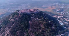 Drone footage of a hill with the Arulmigu Dhandayuthapani Swamy Temple complex in Palani city, Tamil Nadu, India, believed to be the home of Murugan, a Hindu god, lowland behind and mountains in background. The camera is facing down at the hill and isturning around it while tilting up.