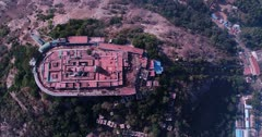 Drone footage of the Arulmigu Dhandayuthapani Swamy Temple complex in Palani city, Tamil Nadu, India, believed to be the home of Murugan, a Hindu god, the lowland behind it and the city buildings before it. The camera is facing down at birdview angle over the temple and is going away from it over the city while tilting up.