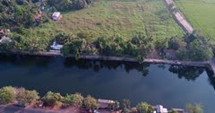 Drone footage of a strip of houses with trees around along a water canal that turns into a canal of common water hyacinths, Eichhornia crassipes, near Alappuzha, Kerala, India. The camera is facing down at the houses and is going sideway along them descending towards the end.