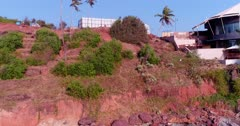 Drone footage of the coastal area in Anjuna, Goa, India, with a few bush trees growing on reddish soil and the Nyex Beach Club building nearby. The camera is facing down at the coast and is going backward while ascending.