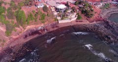 Drone footage of the coastal area in Anjuna, Goa, India, with a few bush trees growing on reddish soil, waves breaking on its rocky beach and the Nyex Beach Club building nearby. The camera is facing down at the coast and is going towards it while panning.