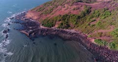 Drone footage of the coastal area in Anjuna, Goa, India, with a few bush trees growing on reddish soil and waves breaking on its rocky beach. The camera is facing down at the beach and is going backward over the water while panning.