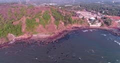 Drone footage of the coastal area in Anjuna, Goa, India, with a few bush trees growing on reddish soil, waves breaking on its rocky beach and the Nyex Beach Club building nearby. The camera is facing down at the coast and is going towards it while tilting down.
