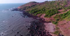 Drone footage of the coastal area in Anjuna, Goa, India, with a few bush trees growing on reddish soil, waves breaking on its rocky beach and a white shrine built on top of rock. The camera is facing the beach at 3/4 angle and is going sideway towards it while descending.