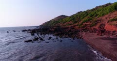 Drone footage of the coastal area in Anjuna, Goa, India, with a few bush trees growing on reddish soil, waves breaking on its rocky beach and a white shrine built on top of rock. The camera is facing the beach at 3/4 angle and is going sideway over the water while ascending.