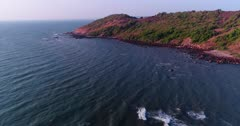 Drone footage of the coastal area in Anjuna, Goa, India, with a few bush trees growing on reddish soil and waves breaking on its rocky beach. The camera is facing the coast and is panning towards the sea.