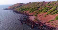 Drone footage of the coastal area in Anjuna, Goa, India, with a few bush trees growing on reddish soil and waves breaking on its rocky beach. The camera is facing the coast at 3/4 angle and ig going sideway towards it while descending.
