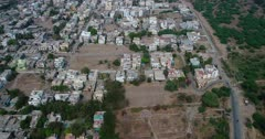 Drone footage of the surroundings of Aurangabad city, Maharashtra, India, with its low residential buildings mostly white and a sandy soccer field close by. The camera is facing down at the buildings and is going backward over them towards the football field.