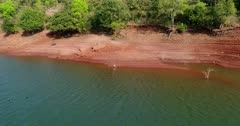 Drone footage of the Koyna river in the surroundings of Tapola, Maharashtra, India, with its tentacle like banks made of red earth making stairs shape covered in vegetation, a white bird is checking the water and 2 black ones are swimming. The camera is going sideway over the water panning around the bird.