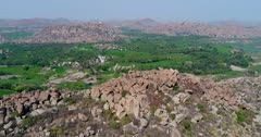 Drone footage of the UNESCO World Heritage temple complex area in Hampi, Karnataka, India, with the rocky landscape and bright green rice fields on the other side of the Tungabhadra river, hills in the background. The camera is going backward while descending over the rocky landscape.