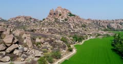 Drone footage of the UNESCO World Heritage temple complex area in Hampi, Karnataka, India, with the rocky landscape and bright green rice fields on the other side of the Tungabhadra river, hills in the background. The camera is going low over the fields before ascending and panning the rocky landscape.