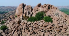 Drone footage of the UNESCO World Heritage temple complex area in Hampi, Karnataka, India, with stack of boulders forming hills and fields in between on the other side of the Tungabhadra river. The camera is turning around a few huge rocks at the top of a hill.