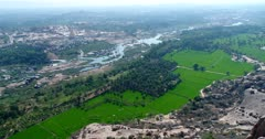 Drone footage of the UNESCO World Heritage temple complex area in Hampi, Karnataka, India, with bright green rice fields, the Tungabhadra river, Hampi village with its main temple Sri Virupaksha and stack of boulders landscape. The camera is panning from Hampi village to the rocky landscape on the other side of the river.