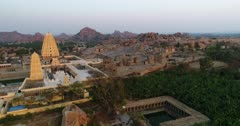 Drone footage of the UNESCO World Heritage temple complex area in Hampi, Karnataka, India, with the many temple ruins on a hill, the newly renovated temple Sri Virupaksha and Hampi village nearby at sunset. The camera is going sideway from the hill towards the village.
