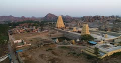 Drone footage of the UNESCO World Heritage temple complex area in Hampi, Karnataka, India, with Hampi village with its main temple Sri Virupaksha next to the Tungabhadra river, granite boulders hill and the many temple ruins behind at sunset. The camera is turning around the main temple showing the village and the rocky hills behind.